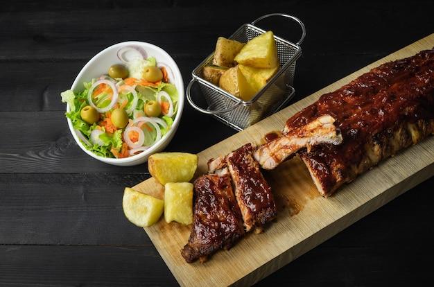 Ребрышки барбекю с картофелем и салатом на деревянной доске
