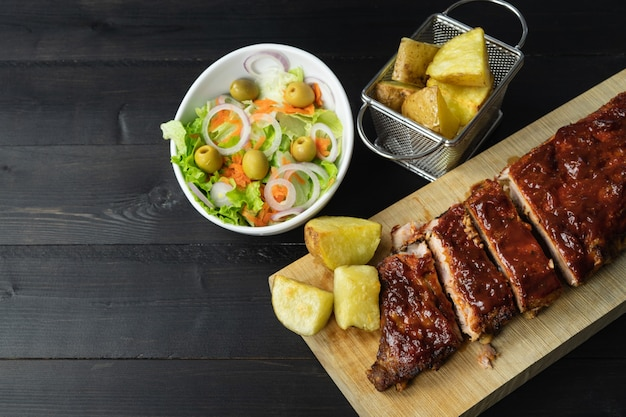 Barbecue ribs with potatoes and salad on a wooden board on a dark background. copy space.