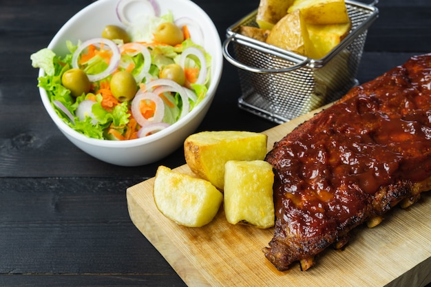 Barbecue ribs with potatoes and salad on a wooden board
