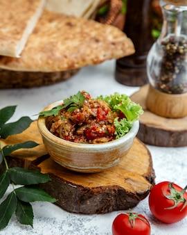 Салат барбекю в глиняной посуде на деревянной конопле