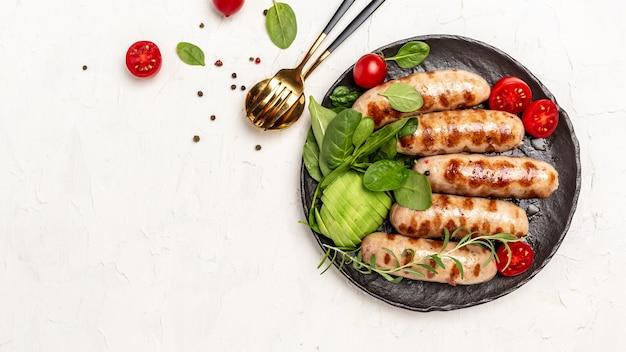 Колбаса барбекю со шпинатом, авокадо и помидорами черри. кетогенная диета. полезные жиры, чистое питание для похудения. кето палеодиета. вид сверху.