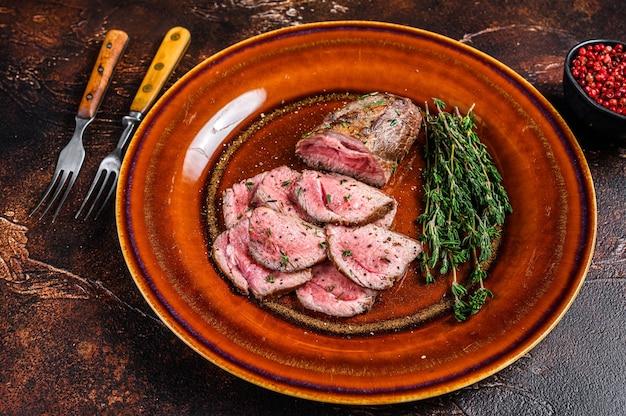 바베큐 얇게 썬 송아지 고기 부드러운 등심 고기 스테이크 접시에. 어두운 배경. 평면도.