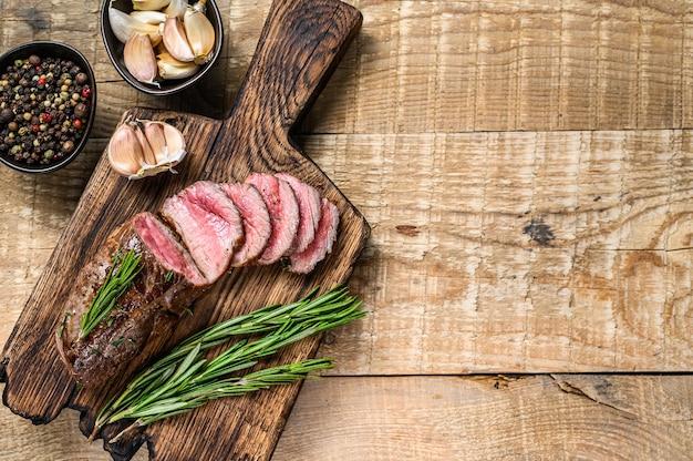 바베큐 슬라이스 송아지 안심 고기 스테이크. 나무 배경입니다. 평면도. 공간을 복사하십시오.