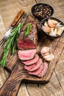 바베큐 슬라이스 송아지 안심 고기 스테이크. 나무 배경입니다. 평면도.