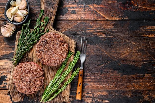 Котлеты из стейка барбекю для бургера из говяжьего фарша на деревянной разделочной доске