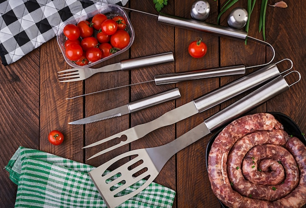 Barbecue tools and sausage on wooden table