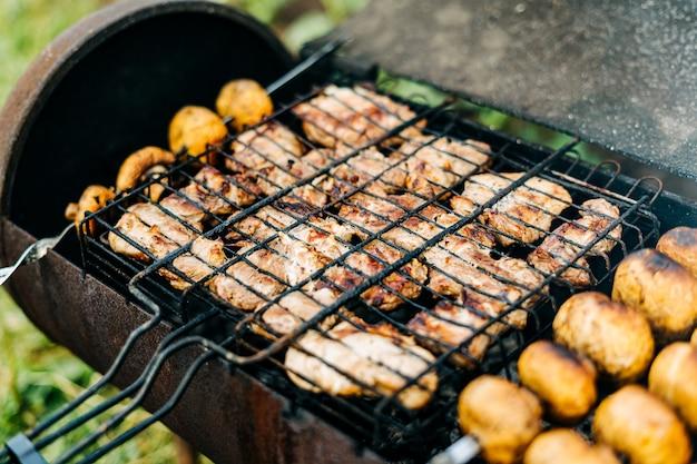 야외 그릴에 구운 고기와 버섯을 곁들인 바베큐는 뒷마당 버섯 꼬치에