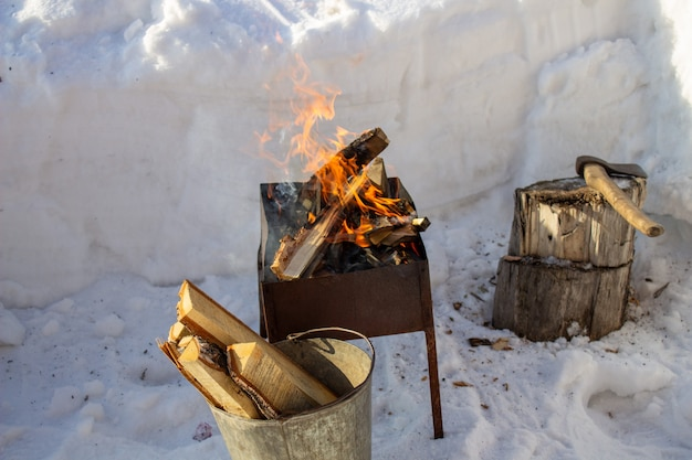 Barbecue with wood in winter on the street. family holiday. fry kebabs
