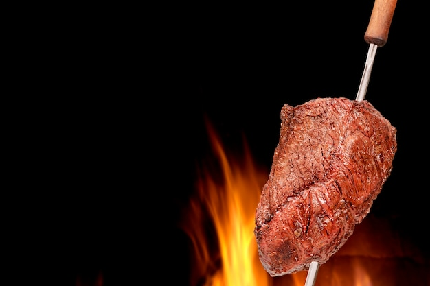 Barbecued picanha barbecue with blurred fire in the background also called churrasco