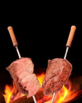 배경에 흐릿한 불이 있는 바베큐 피칸하 바베큐