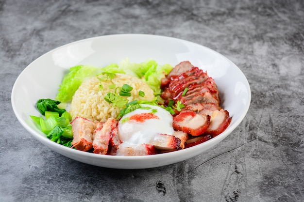 Barbecued red pork and crispy pork in red sauce, served with rice and vegetable on white plate,