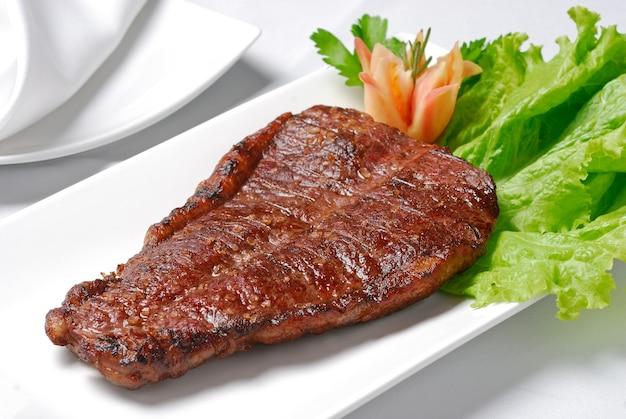 Приготовленное на гриле мясо в белой миске на столе