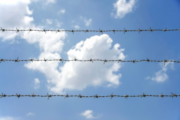 Barbed fence with blue sky and white cloud in bright day
