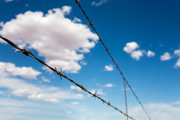 Barbed wire againdt blue cloudy sky.