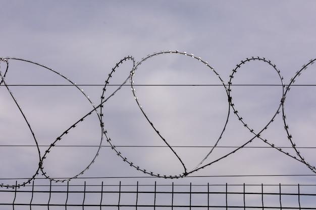 曇り空を背景に有刺鉄線。刑務所のフェンスからの有刺鉄線の囲い。