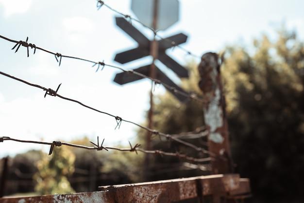 Забор из колючей проволоки против драматического темного неба. городская дорога уличный знак