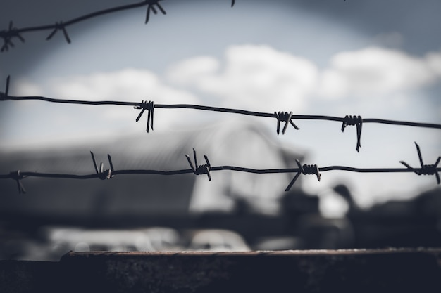 Забор из колючей проволоки против драматического темного неба.
