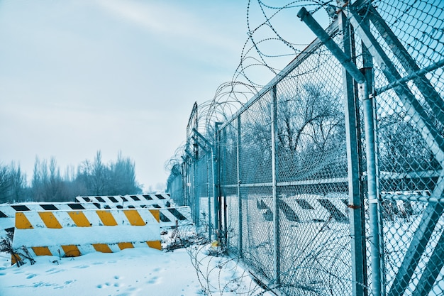 Barbed wire fence on border in winter private object near highway concrete road blocks on ground clo...