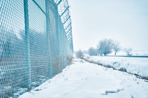 Barbed wire fence on border in winter private secured object near highway maximum security detention...