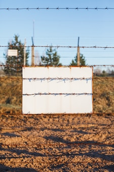 Barbed wire fence protects the danger zone. white sign board