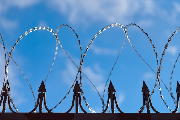 Barbed wire on fence, steel grating fence, metal fence wire. coiled razor wire with sharp steel barbs