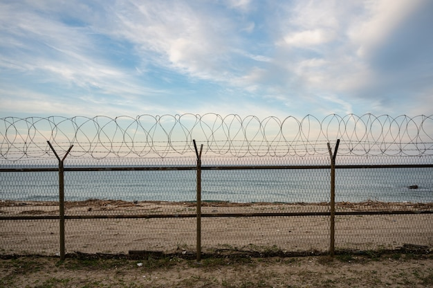 Barbed wire mesh fence on seashore at evening. concept of freedom