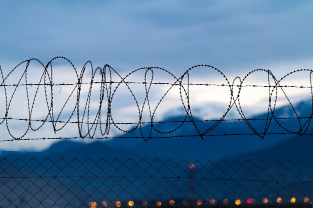 Barbed wire on mountains background in the evening