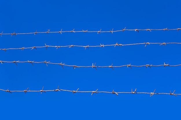 푸른 하늘을 배경으로 철조망 프리미엄 사진