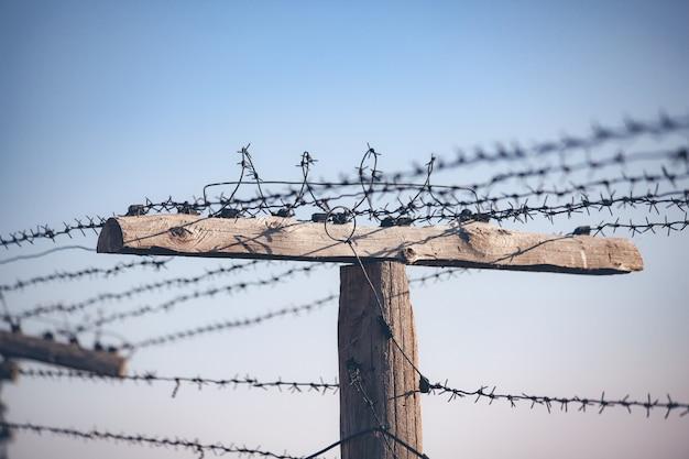 Колючая проволока на заборе с голубым небом