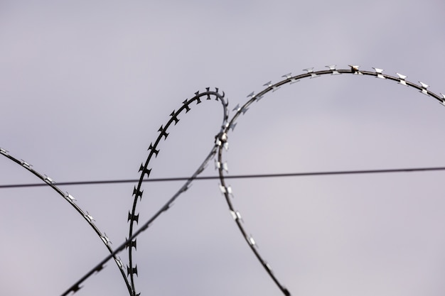 Barbed wire on the sky background. metal wire. selective focus