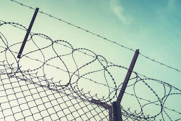 Стена из колючей проволоки против иммиграции. стена с колючей проволокой на границе 2 стран. частная или закрытая военная зона на фоне голубого неба.