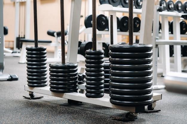 바벨 디스크는 체육관에서 줄에 쌓여 있습니다.