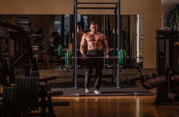 バーベルトレーニング。 6パック、完璧な腹筋、肩、上腕二頭筋、上腕三頭筋、胸を持つボディービルダーの運動選手。