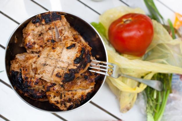 Барбекю мясо на гриле со спелыми свежими красными помидорами