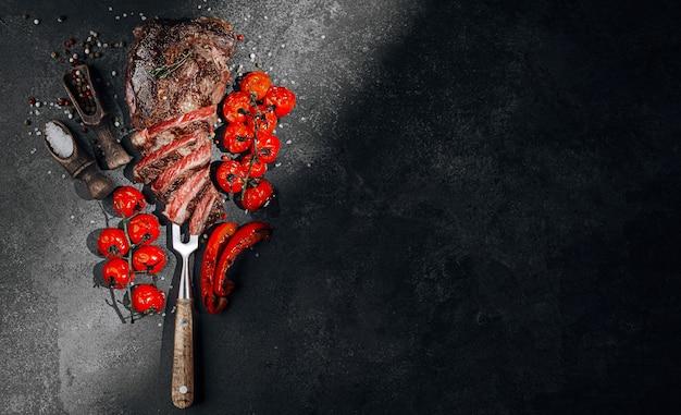 黒のスレートボードにバーベキューステーキ Premium写真