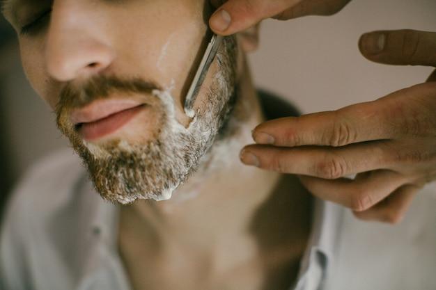 理容師は顔にシェービングクリームを適用します