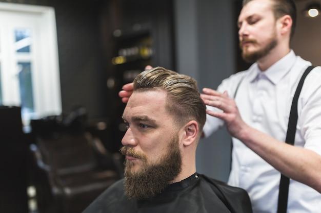 Barbiere applicando la mousse sui capelli del cliente