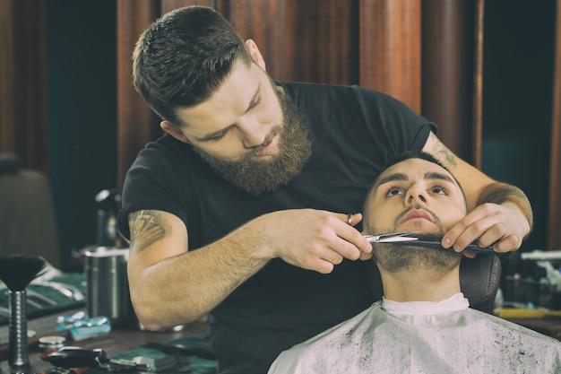 Парикмахерская на работе. горизонтальный портрет красивой бородатой и татуированной парикмахера, работающей