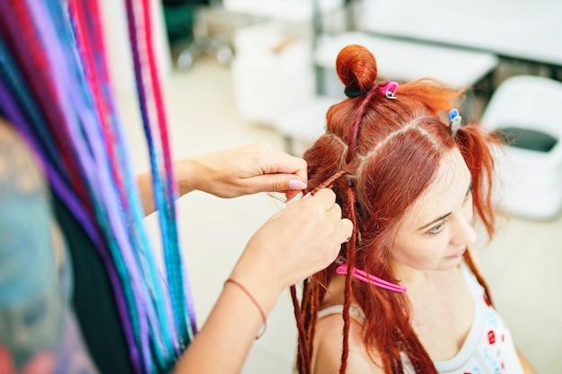 理髪店の三つ編みドレッドヘア赤毛の女の子はファッショナブルな三つ編みドレッドヘアを安全な取り外し可能なドレッドヘアにします...