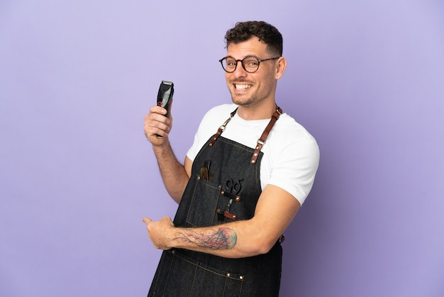 Barber caucasian man in an apron isolated on purple pointing back