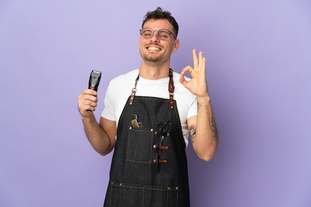 손가락으로 확인 표시를 보여주는 보라색에 고립 된 앞치마에 이발사 백인 남자
