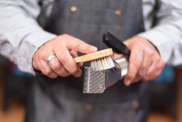 Barber cleaning electric hair clipper.