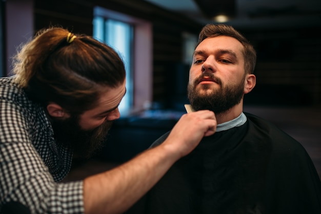 Barber combing beard of the client man in salon cape at the barbershop