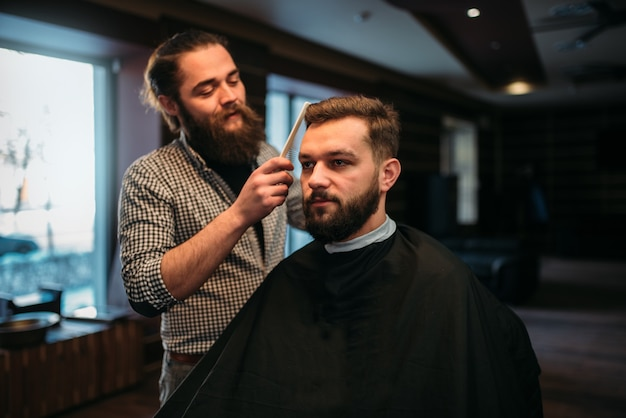 Barber combing hair of the client man in salon cape.