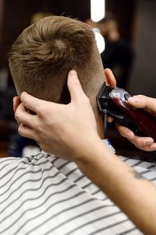 Парикмахер режет клиента в стильной парикмахерской. мужская стрижка бритвой