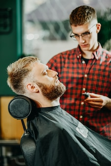 The barber cuts his beard to a man in the salon