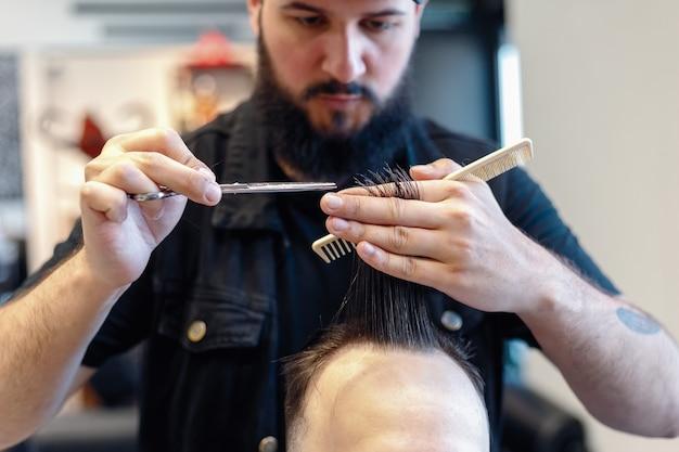이발사는 가위로 고객의 머리를 자른다. 확대. 매력적인 남성이 이발소에서 현대적인 이발을 하고 있습니다. 핸드헬드 샷. 4k.
