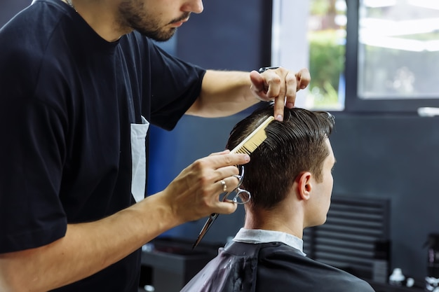 이발사는 가위로 고객의 머리카락을 자릅니다. 확대. 매력적인 남성 이발소에서 현대 이발을 받고있다.