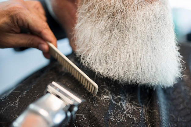 Barber cutting beard to client in salon