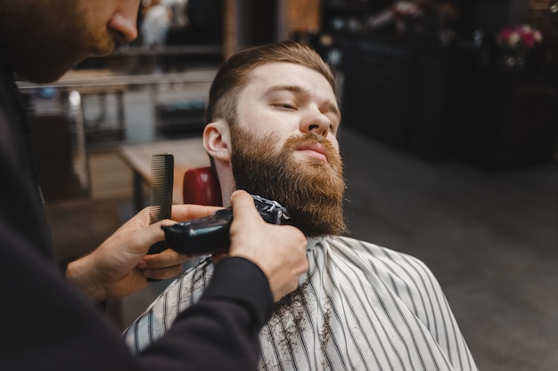 Barber cutting beard to a client